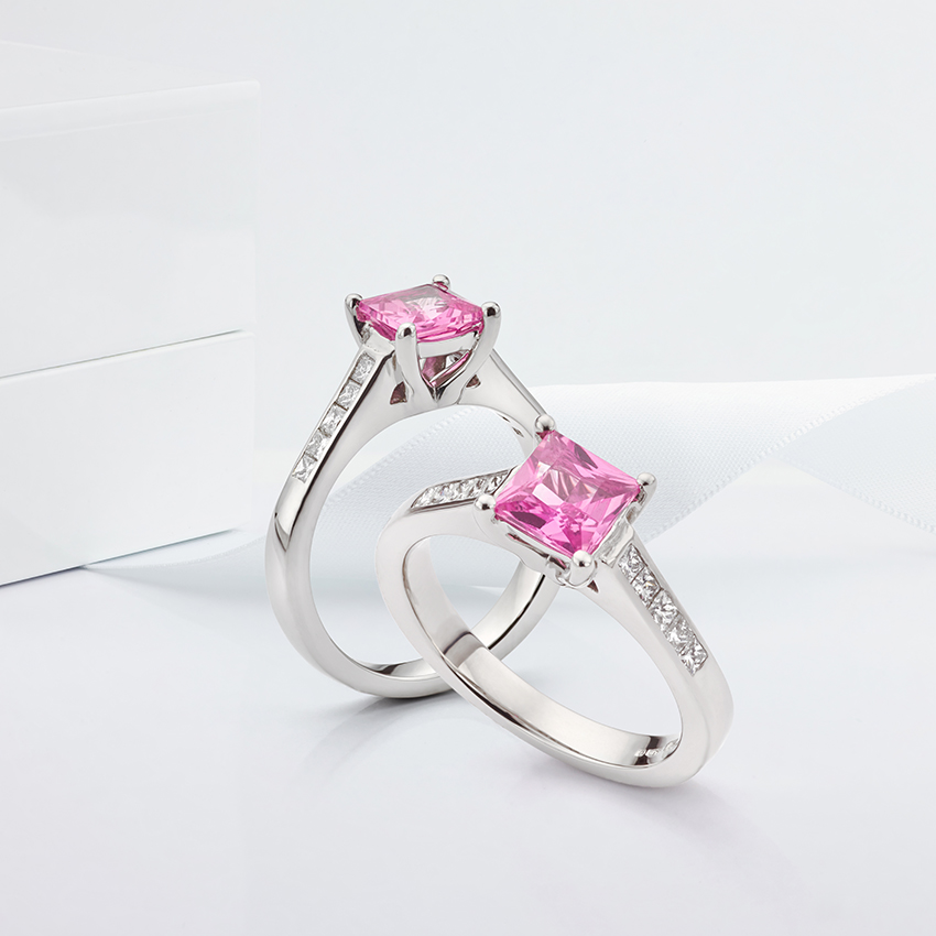 Pink fliss engagement ring shown with diamond shoulders and pink sapphire