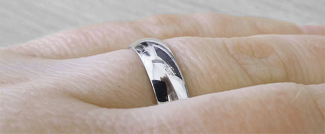 A regular D shaped medium weight wedding ring on the finger