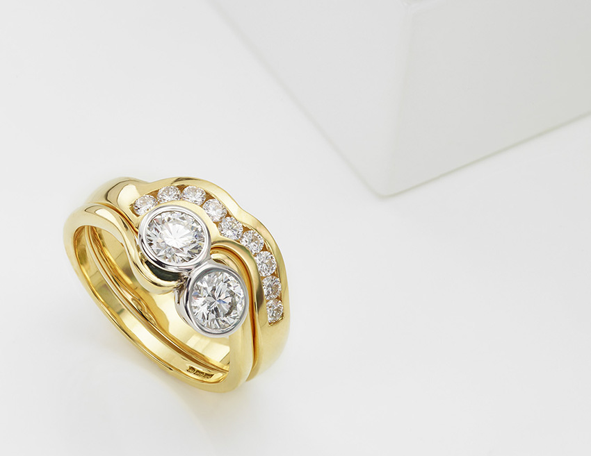 Two stone yellow gold ring with platinum bezel setting and shaped wedding band