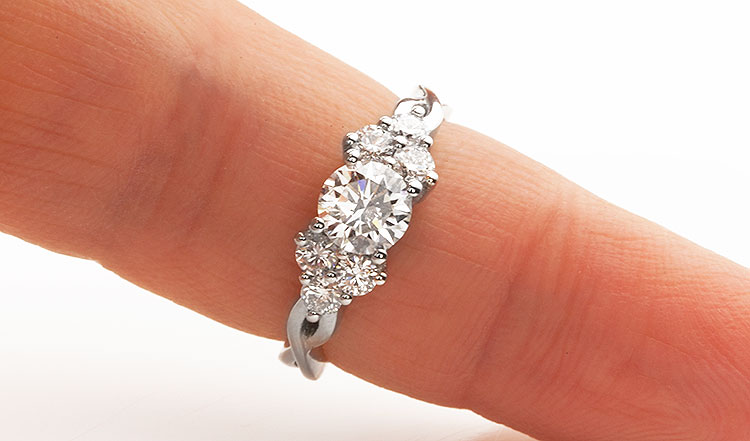 front facing view of plaited shoulder ring design with small outer diamonds on the finger