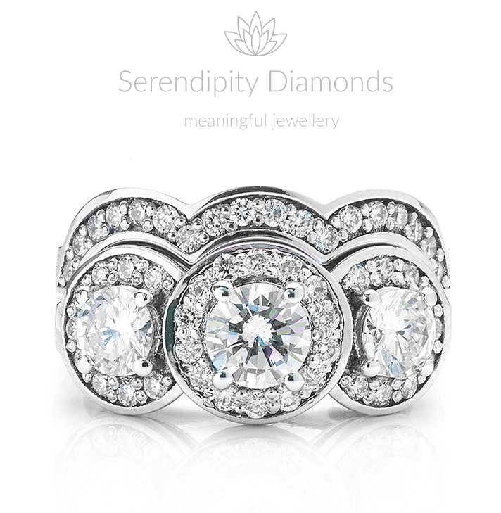 Diamond ring set featuring a 3 stone diamond halo engagement ring with shaped wedding ring