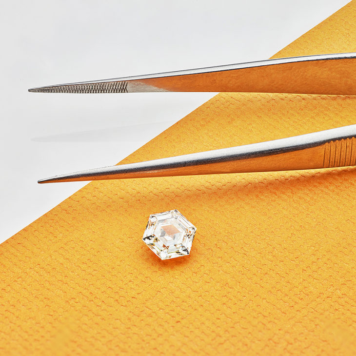 Hexagonal diamonds with step faceting next to diamond tweezers