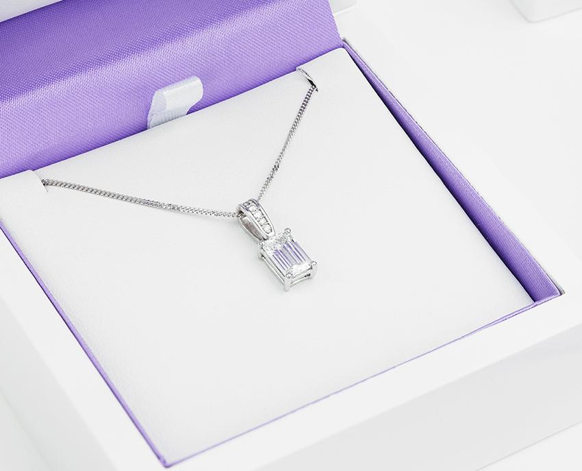 Emerald cut diamond pendant with a 1 carat Emerald and diamond loop