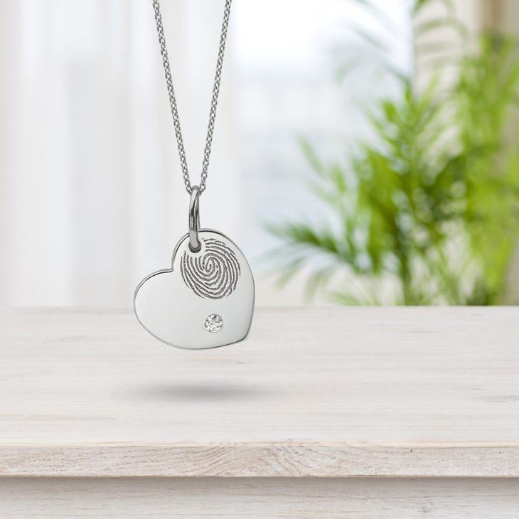 Fingerprint jewellery pendant over table