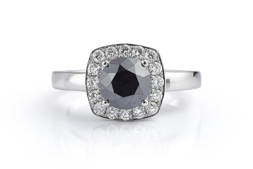 Treated 1 carat black diamond halo engagement ring surrounded by white diamonds.
