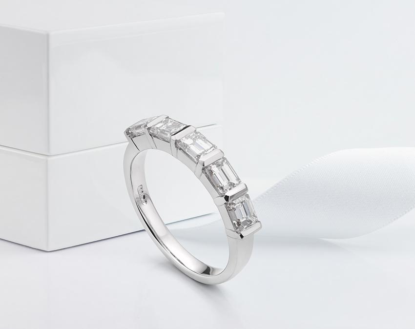 Emerald cut half diamond eternity ring