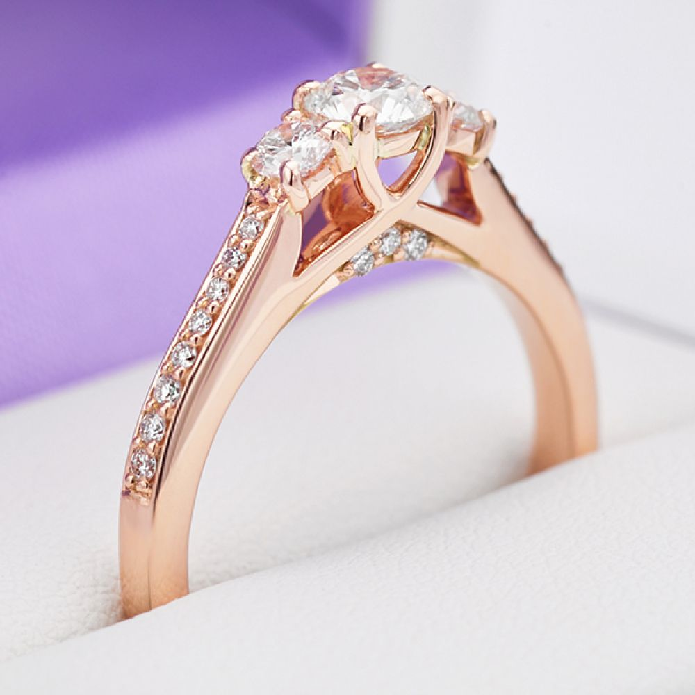 Showing the boxed ring in Rose Gold, set with three diamonds with secret diamond set engraving