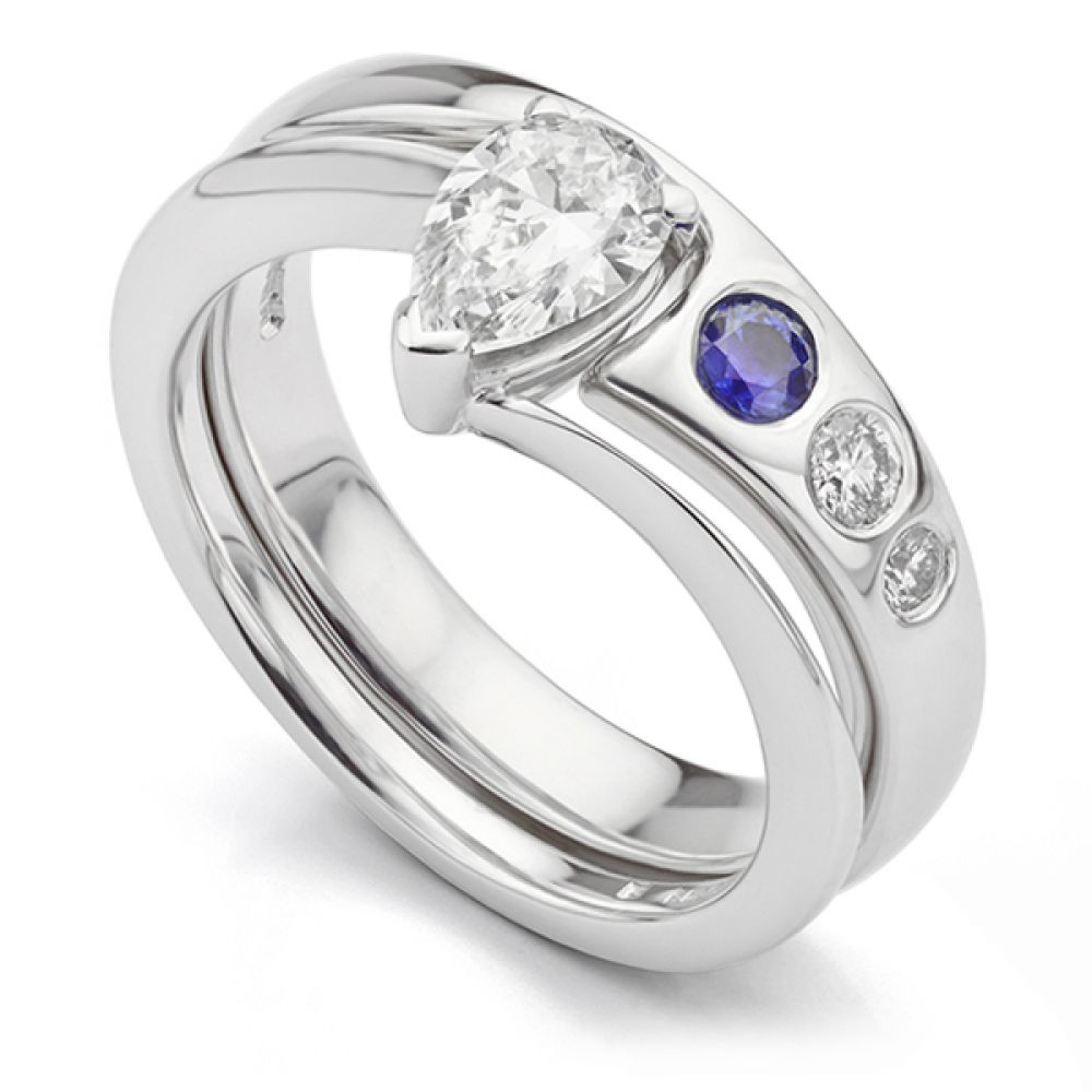 Blue Sapphire and Diamond Shaped Wedding Ring. Features flush set blue sapphires and diamonds with a shaped design to fit around a Pear shaped solitaire engagement rings.