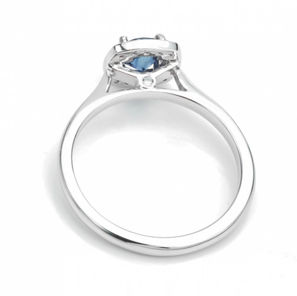 Royal blue sapphire and diamond cushion halo engagement ring side view
