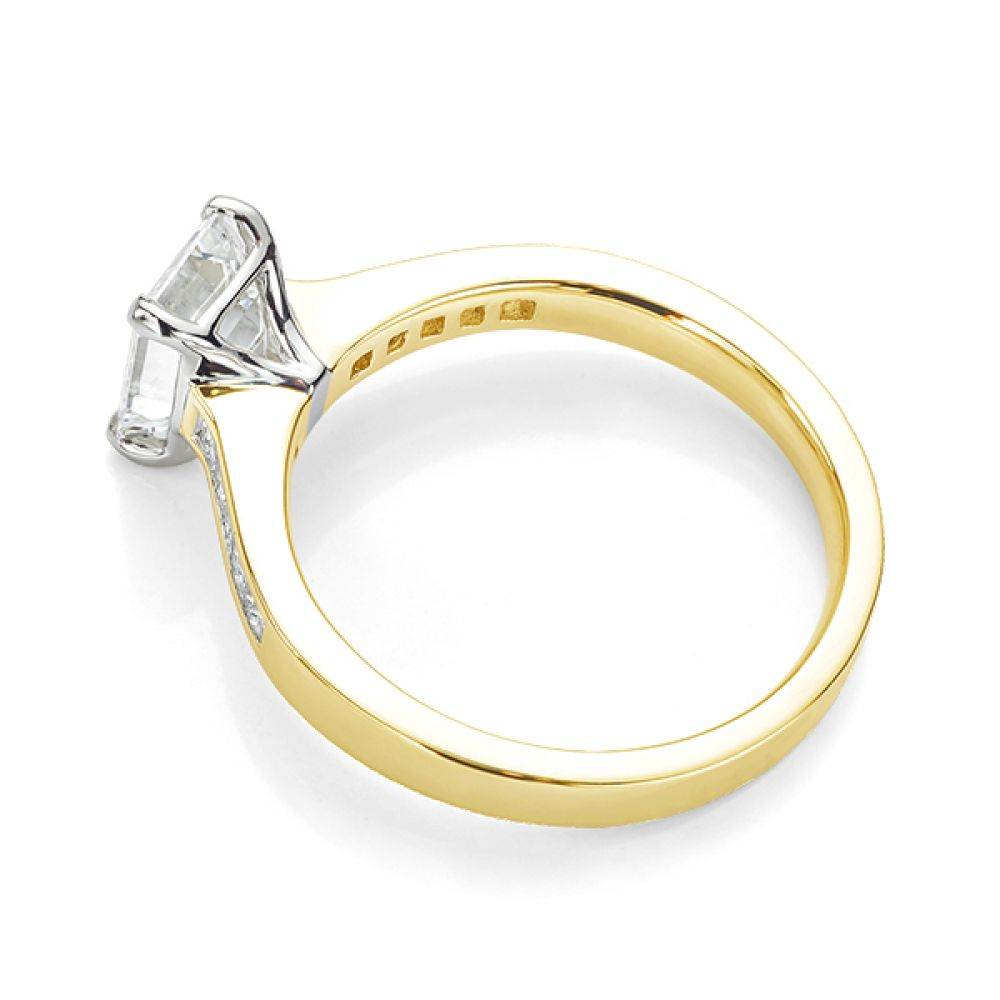 Emerald cut diamond engagement ring with Princess cut diamond shoulders yellow gold side view