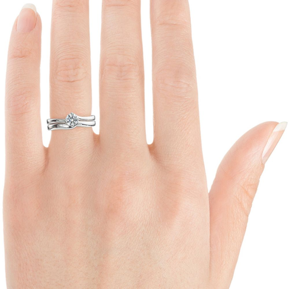 Closeup of twist engagement ring with matching shaped wedding ring