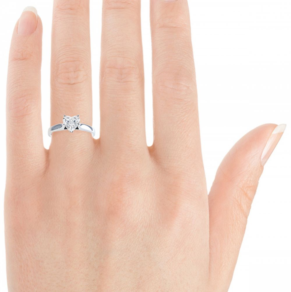 Heart shaped solitaire engagement ring on finger