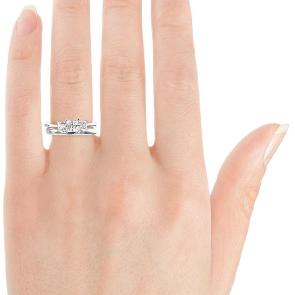 Showing a plain wedding ring sat with the 1 carat version of the Princess cut trilogy ring on the hand