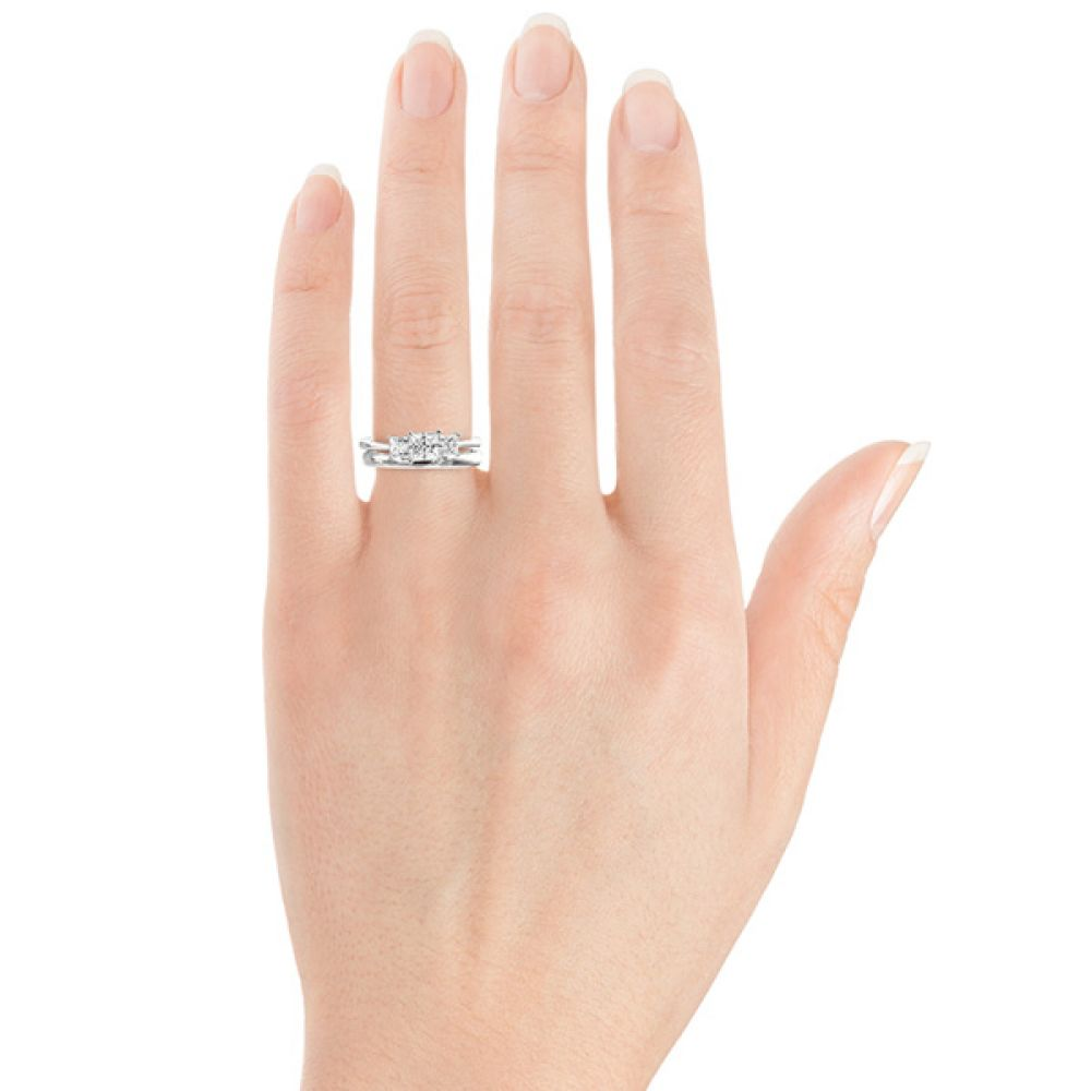 2.5mm slight court wedding ring shown alongside a trilogy engagement ring on finger
