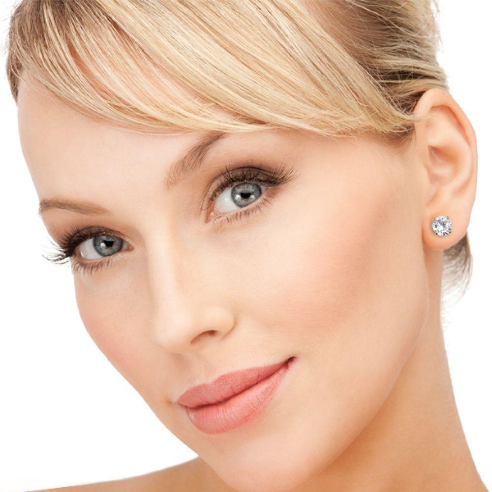 Four claw diamond stud earrings shown in ear
