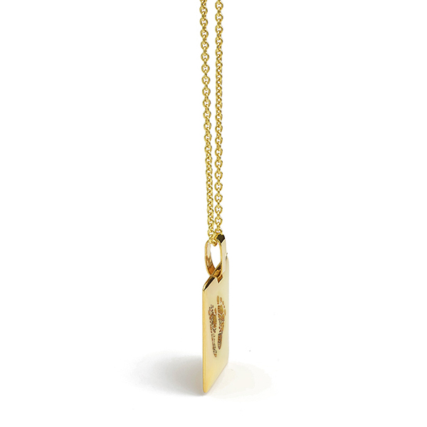 Side view of gold footprint engraved pendant